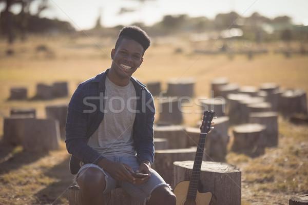 Portré férfi tart okostelefon ül fa Stock fotó © wavebreak_media