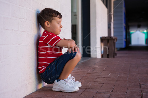 Side view of boy crouching by wall Stock photo © wavebreak_media