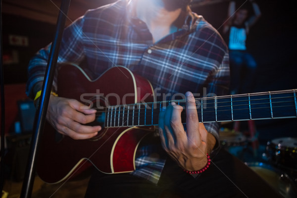 Stock photo: Mid section of musician playing guitar on stage
