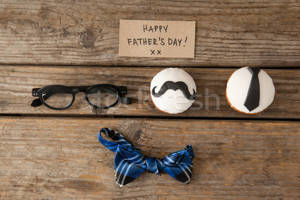 Happy fathers day text on paper by decorated cupcakes and eyeglasses at table Stock photo © wavebreak_media