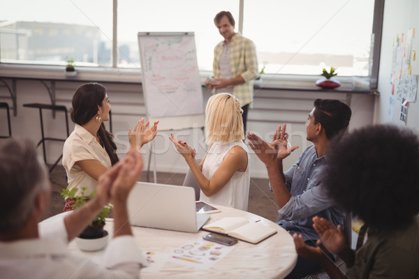 Colleagues applauding for businessman giving presentation Stock photo © wavebreak_media
