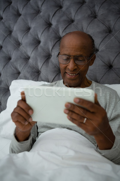 Senior man using digital tablet while resting on bed Stock photo © wavebreak_media