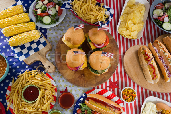 Hot dogs and burgers on wooden table with 4th july theme Stock photo © wavebreak_media
