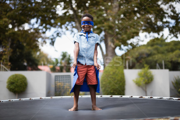 Boy in superhero costume standing on trampoline Stock photo © wavebreak_media