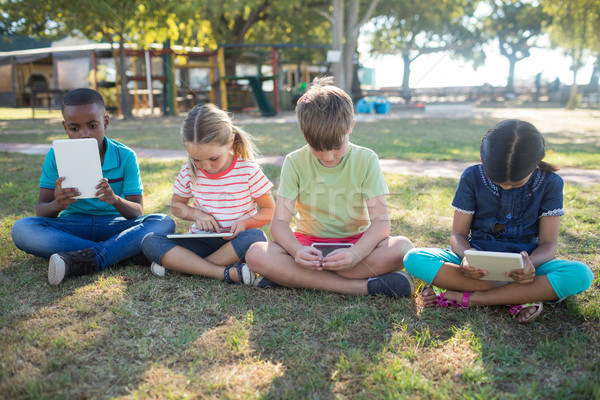 Gyerekek táblagép ül füves mező park Stock fotó © wavebreak_media