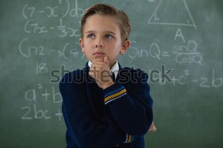 Smiling boy against blank greenboard Stock photo © wavebreak_media