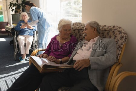 Female doctor explaining with clipboard to seniors sitting on chairs Stock photo © wavebreak_media