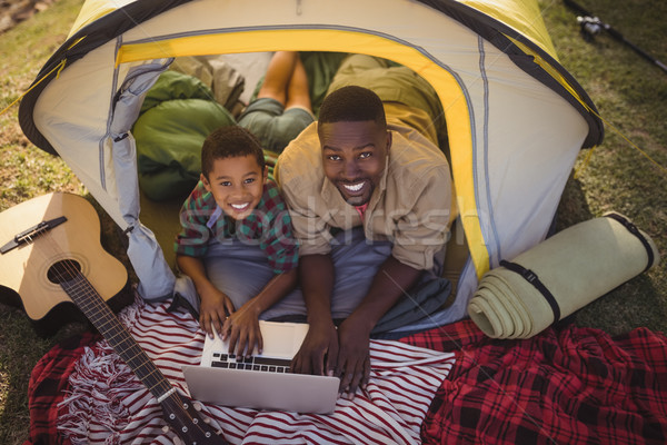 Smiling father and son using laptop in tent Stock photo © wavebreak_media