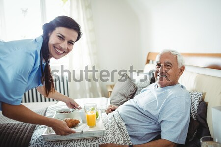 Cropped hand of female doctor serving food to senior patient relaxing on bed Stock photo © wavebreak_media