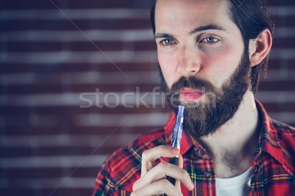 Hipster with electronic cigarette looking away Stock photo © wavebreak_media