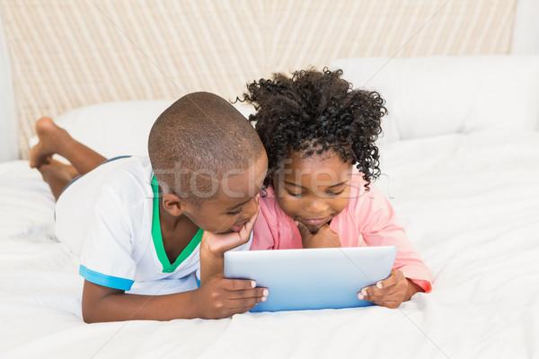 Boldog testvérek tabletta ágy otthon lány Stock fotó © wavebreak_media