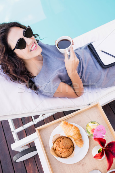 Young woman having cup of tea near poolside Stock photo © wavebreak_media