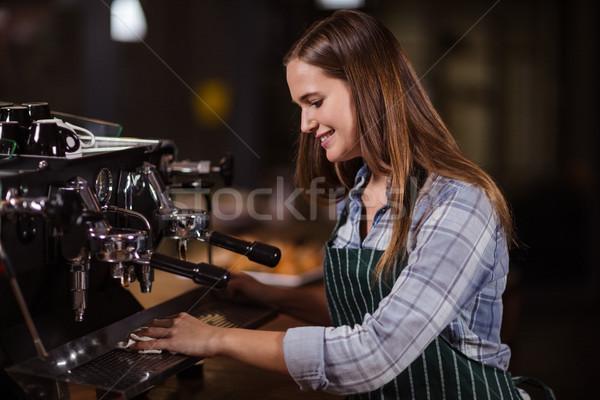 Smiling barista cleaning coffee machine Stock photo © wavebreak_media