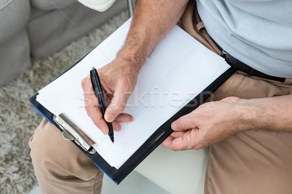 Człowiek piśmie notatnika domu pióro komunikacji Zdjęcia stock © wavebreak_media