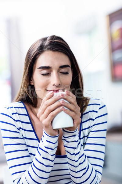 Beautiful young woman with eyes closed holding mug Stock photo © wavebreak_media
