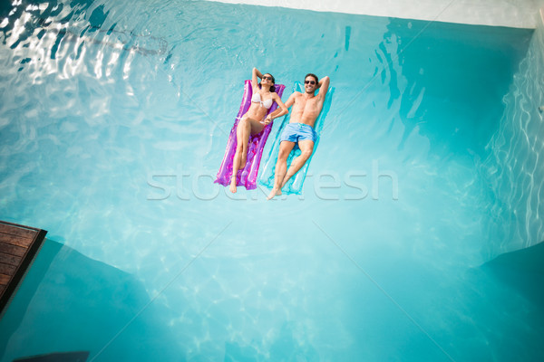 Couple relaxing on inflatable raft at swimming pool Stock photo © wavebreak_media