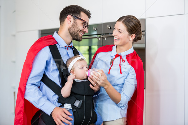 Cheerful couple in superhero costume feeding milk to daughter Stock photo © wavebreak_media