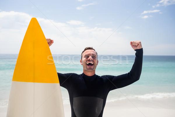 Boldog férfi szörfdeszka áll tengerpart karok Stock fotó © wavebreak_media