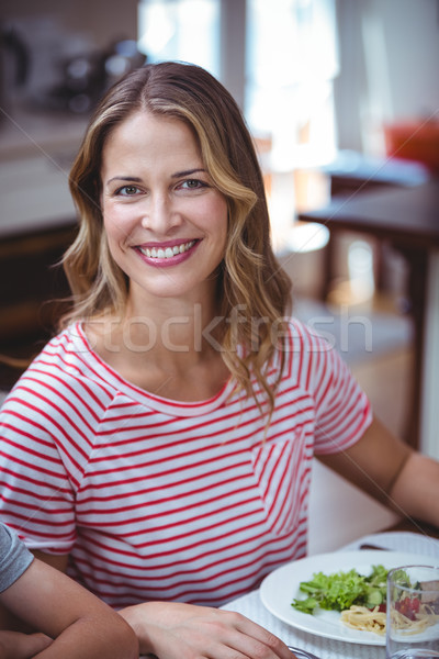 Smiling woman sitting at dining table Stock photo © wavebreak_media
