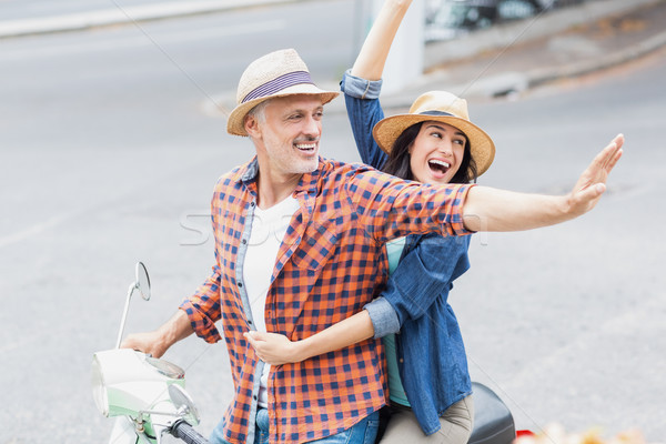 Stock photo: Excited couple waving hands on moped