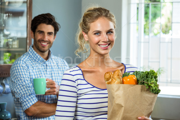 Woman carrying grocery bag while man with coffee cup in kitchen  Stock photo © wavebreak_media
