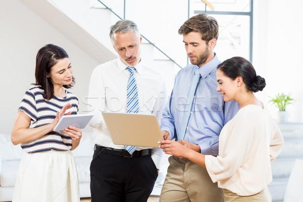 Business people interacting using digital tablet and laptop  Stock photo © wavebreak_media
