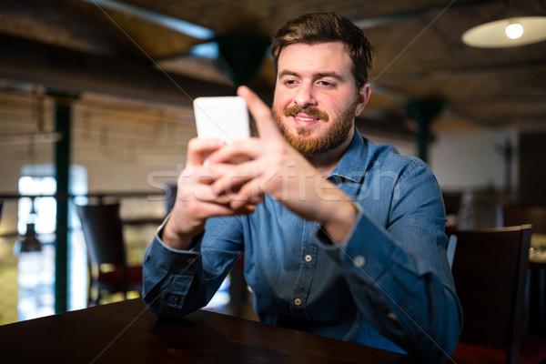Man text messaging on mobile phone Stock photo © wavebreak_media