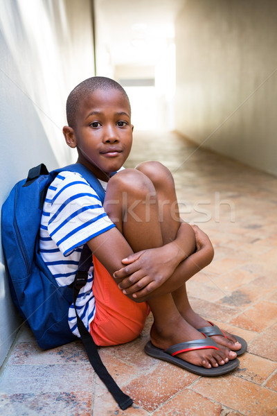 Elementary boy sitting on corridor in school Stock photo © wavebreak_media