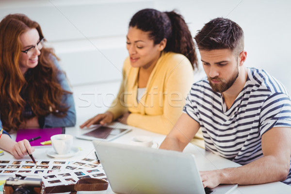 Editor using laptop with colleagues talking at creative office Stock photo © wavebreak_media