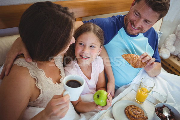 Parents sitting on bed with daughter and having breakfast Stock photo © wavebreak_media