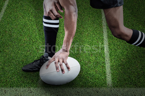 Composite image of low section of sportsman holding rugby ball Stock photo © wavebreak_media