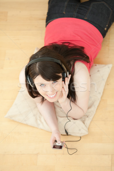 Merry woman listening music lying down on the floor Stock photo © wavebreak_media