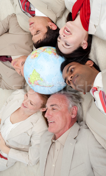 Business team lying on the floor around a terrestrial globe Stock photo © wavebreak_media