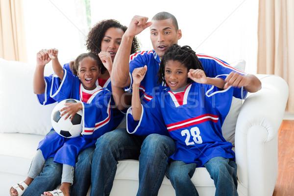 Afro-American family celebrating a goal at home Stock photo © wavebreak_media