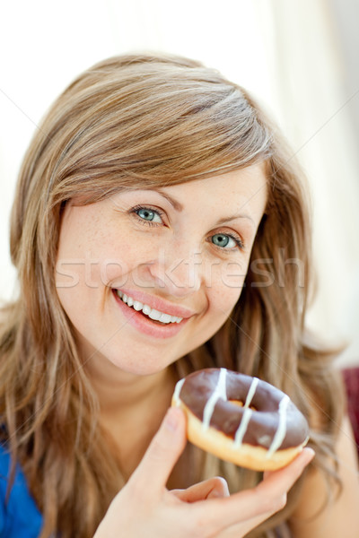 Smiling woman is eating a donut on a sofa  Stock photo © wavebreak_media