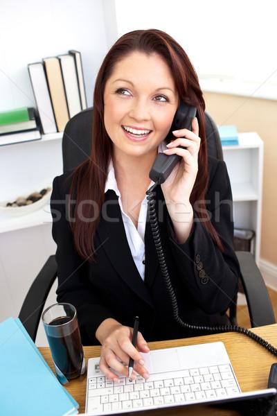 Tolakodó üzletasszony beszél telefon laptopot használ asztal Stock fotó © wavebreak_media