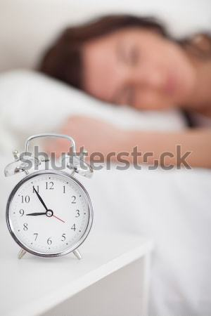 Beautiful red-haired woman waking up thanks to an alarm clock in the bedroom Stock photo © wavebreak_media