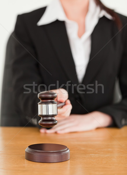 Young woman using a gavel while sitting at a desk against a white background Stock photo © wavebreak_media