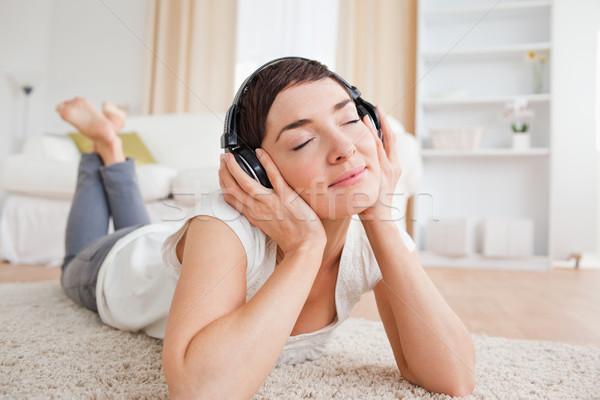 Serene woman listening to music while lying on a carpet Stock photo © wavebreak_media