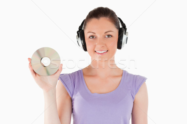Good looking woman with headphones holding a CD while standing against a white background Stock photo © wavebreak_media