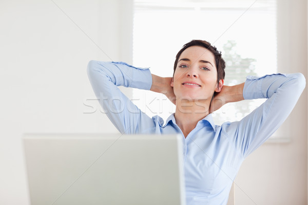 Short-haired relaxed businesswoman with a laptop looking into the camera in an office Stock photo © wavebreak_media