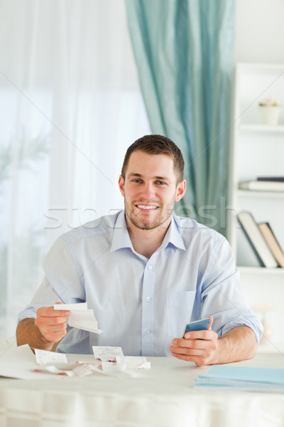Young businessman with hand calculator checking invoices Stock photo © wavebreak_media