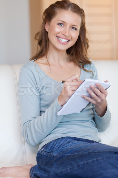 Smiling woman taking notes on her couch Stock photo © wavebreak_media