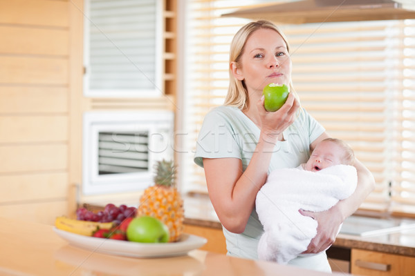 Young woman chewing on apple while holding baby on her arms Stock photo © wavebreak_media