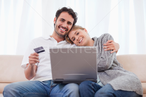 Smiling couple shopping online in their living room Stock photo © wavebreak_media