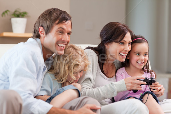 Delighted family playing video games together in a living room Stock photo © wavebreak_media