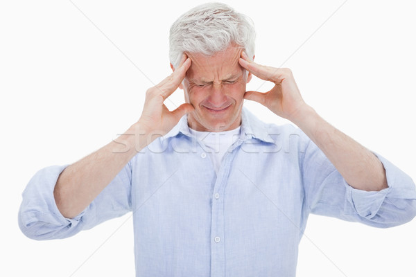 Exhausted man having a strong headache against a white background Stock photo © wavebreak_media