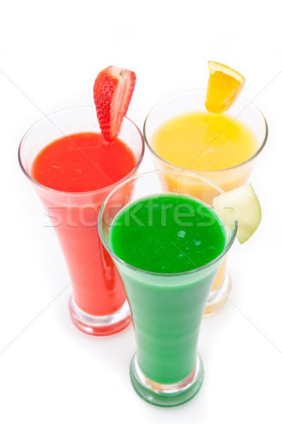 Three glasses full of fruit juice with fruits pieces against white background Stock photo © wavebreak_media