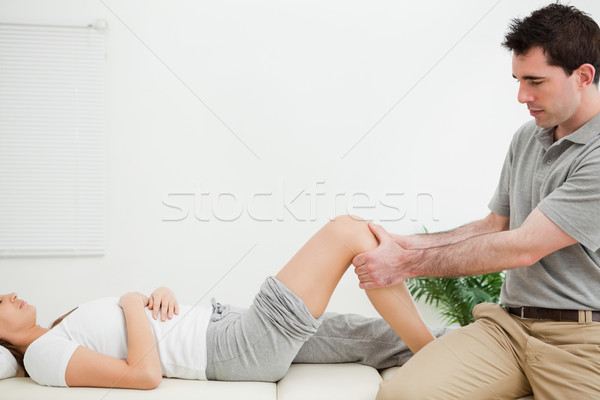 Physiotherapist sitting while massaging a knee in a room Stock photo © wavebreak_media