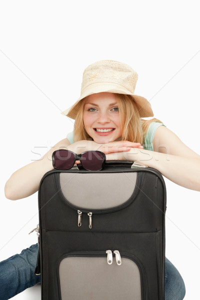 Woman leaning on a suitcase while sitting against white background Stock photo © wavebreak_media